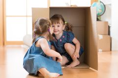 Children little girls playing inside box. After moving in new flat royalty free stock photos