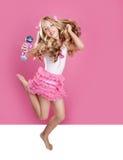 Children little star singer like fashion doll. Blond singer star girl like fashion doll with mic jumping high Stock Images