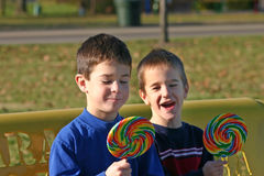 Children with Lollipops. Two boys happy to be eating lollipops stock photo