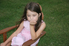 Children - Lonely Girl. Sad little girl sits in a chair on the lawn Stock Image