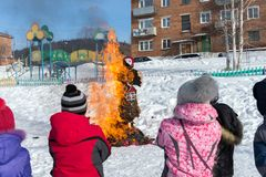 Children look at the burning of a Shrovetide doll in Russian folk costume, during a traditional national holiday of Seeing off. BELOGORSK, Kemerovo region/ RF stock photo