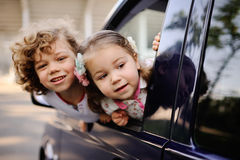 Children look out from a car window. Little boy and girl playing inside a minivan.family trip stock photography