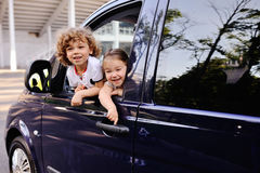 Children look out from a car window. Little boy and girl playing inside a minivan.family trip royalty free stock photo