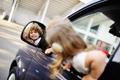 Children look out from a car window. Little boy and girl playing inside a minivan.family trip stock photo