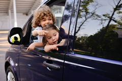 Children look out from a car window. Little boy and girl playing inside a minivan.family trip royalty free stock images