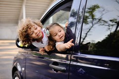 Children look out from a car window. Little boy and girl playing inside a minivan.family trip stock photos