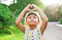 Children look pass hand heart. Little girl happyness in nature sunshine Stock Photos
