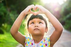 Children look pass hand heart. And sunshine Royalty Free Stock Photo