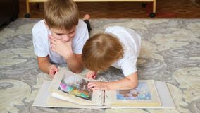 Children look pictures of a family photo album. Children look pictures of wedding photo album parents stock footage