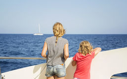 Children look at the sea from the deck of a boat Stock Photography