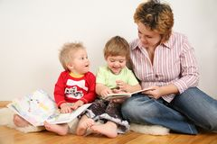 Children looking books with mother. Two children looking books with mother Royalty Free Stock Photos