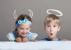 Children looking at camera from behind the table Royalty Free Stock Images