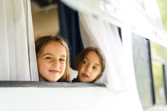 Children are looking through caravan or camper motorhome window. Stock Image