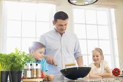 Children looking at father preparing food in kitchen Royalty Free Stock Photography