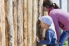 Children are looking through the hole in the fence stock photo