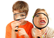 Children looking through magnifying glasses. Brother and sister looking through magnifying glasses isolated on white background Stock Photo