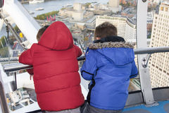 Children looking out from the London eye. Two children in London Eye capsule looking down across london Stock Photo