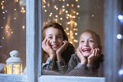 Children looking out the window. Smiling children looking out the window, at night Stock Photo