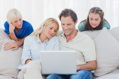 Children looking at parents using a laptop Royalty Free Stock Photos