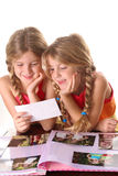 Children looking at photos together vertical. Shot of children looking at photos together vertical Royalty Free Stock Photo