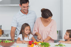 Children looking at their mother preparing vegetables Royalty Free Stock Images