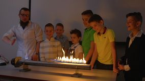 Children looks at the experiment with fiery loudspeaker and music. Children makes experiment with Ruben`s tube. The fire is dancing to the beat of music in flame stock video footage