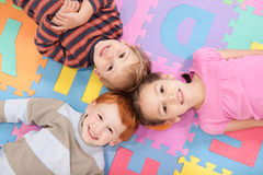 Children lying on backs on fun kids alphabet mat. Three kids having fun lying on backs on alphabet mat Royalty Free Stock Photos