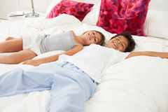 Children Lying On Bed In Pajamas Together Royalty Free Stock Photo
