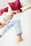 Children Lying On Bed In Pajamas Together stock photos