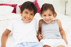 Children Lying On Bed In Pajamas Together Stock Image