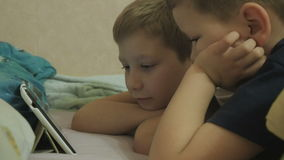Children lying on a bed and watching the show. Boys looking at tablet. kids online at home stock video