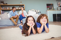 Children lying on carpet while parents sitting in background Stock Photography
