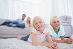 Children lying on the carpet. And smiling at camera Royalty Free Stock Photos