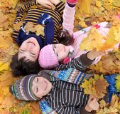 Children lying in fall leaves royalty free stock photos