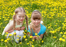 Children lying in field with flower. Royalty Free Stock Photo