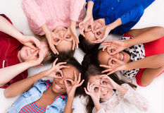 Children lying on the floor head to head with glasses out of fingers Stock Photo