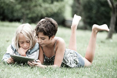 Children lying on the grass looking on the tablet Stock Photos