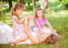 Children lying on green grass outdoors Royalty Free Stock Image