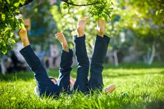 Children lying on green grass in park on a summer day with their legs lifted up to the sky. To the blooming tree. Selective focus. Relaxation happy childhood stock images