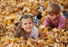 Children are lying and palying in fallen leaves in autumn city park stock photo