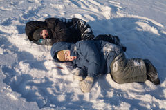 Children lying on snow Royalty Free Stock Photos