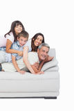 Children lying on their parents on sofa Royalty Free Stock Photos