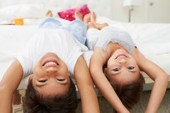 Children Lying Upside Down On Bed In Pajamas Together Stock Photos