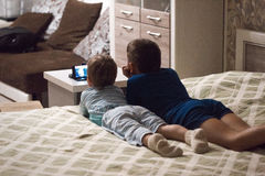 Children lying watch cartoons on your phone. Children lying watch cartoons on your phone royalty free stock photography