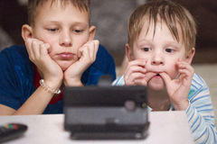 Children lying watch cartoons on your phone. Children lying watch cartoons on your phone stock photos