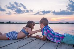 Children lying on the wooden pier and holding hands royalty free stock photography