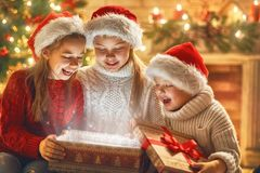 Children with magic gift box. Merry Christmas and Happy Holiday! Cute little children with magic present gift box near tree at home Stock Photos