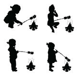 Children make barbecue on fire silhouette illustration. In black Royalty Free Stock Images