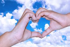 Children make a heart on blue sky background. royalty free stock image