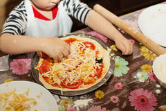 Children make homemade pizza. Children make pizza. Master class for children on cooking Italian pizza. Young children learn to cook a pizza. Kids preparing royalty free stock image